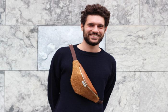 Junger Mann mit Locken trägt braune Bauchtasche für Männer