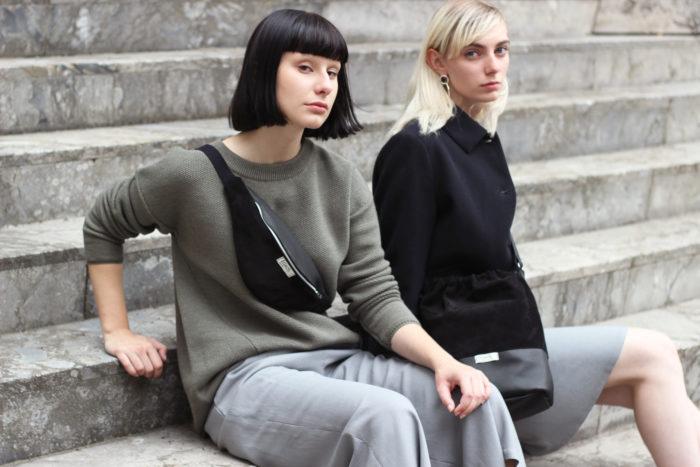 Zwei junge Frauen sitzen auf Treppe und tragen frisch Beutel Bauchtasche und Umhängetasche