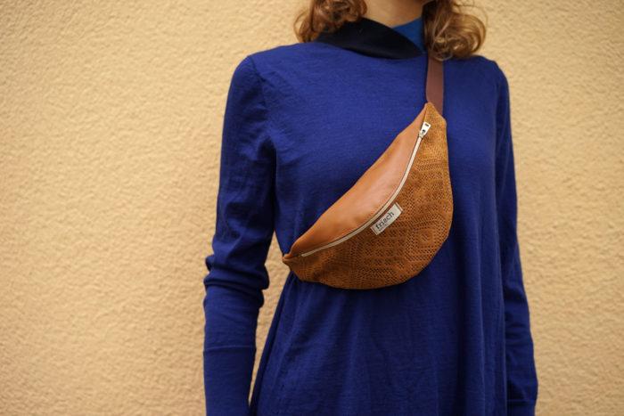 Oberkörper mit blauem Kleid und brauner Bauchtasche mit Boho Muster