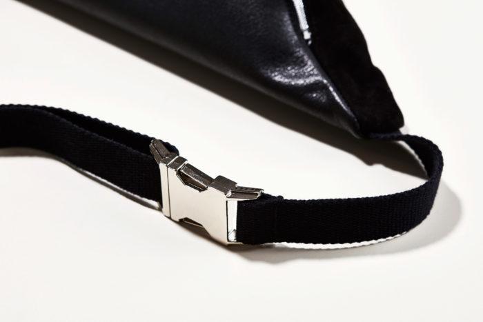 Detail einer schwarzen Bauchtasche mit Silberschnalle und Baumwollgurt