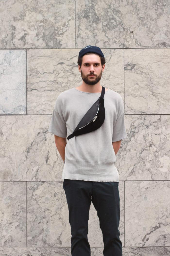 Junger Mann trägt Bauchtasche für Männer aus schwarzem Leder