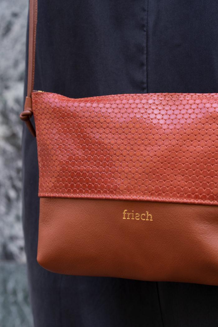Close up von orangeroter Handtasche von frisch mit goldener Prägung