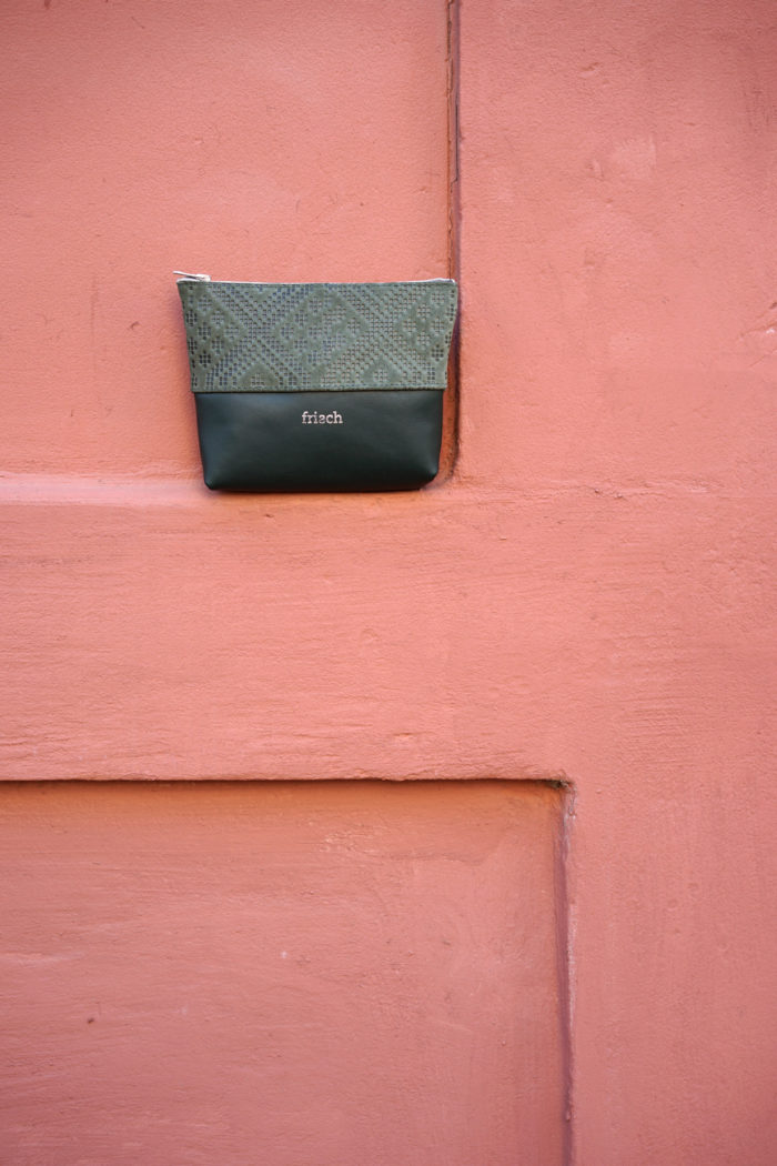 Kleiner Lederbeutel in dunkelgrün vor terracotta farbener Wand