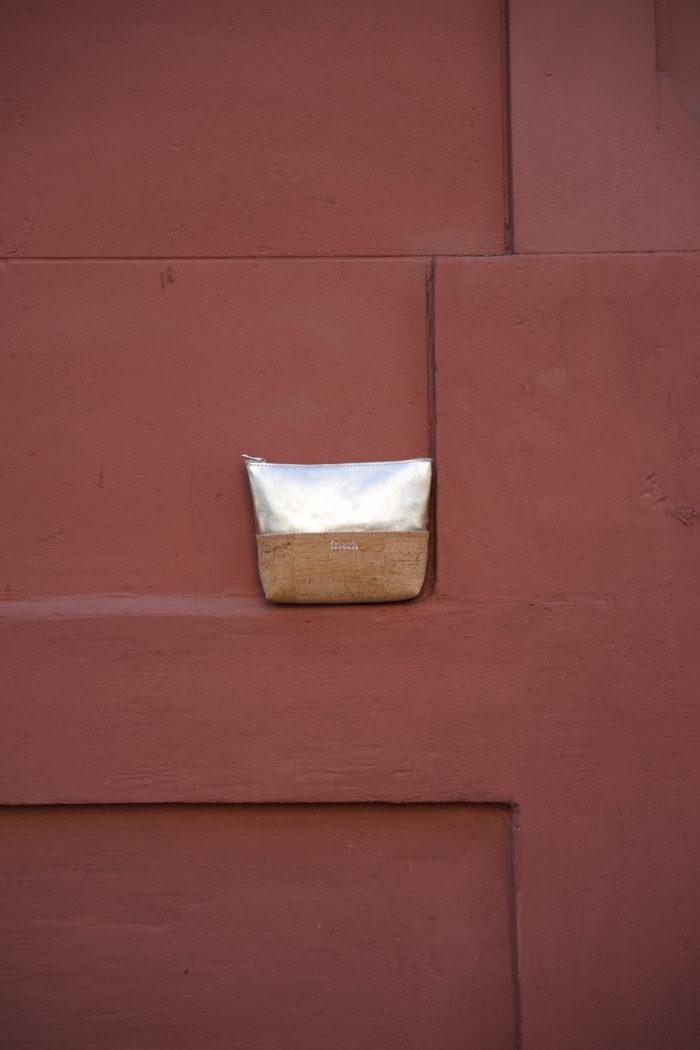Kleiner frisch Beutel aus Kork und silberfarbenem Leder vor roter Wand