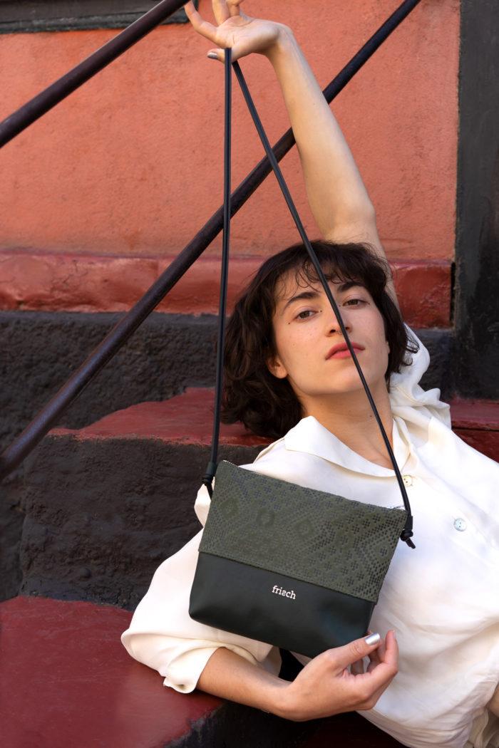 Model zeigt frisch Beutel Handtasche aus dunkelgrünem Leder