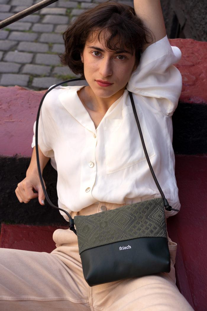 Model mit dunkelgrüner kleiner Handtasche von frisch Beutel