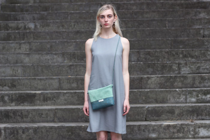 Handtasche Kiesel aus Kork und mit Leder getragen von Model auf Treppe