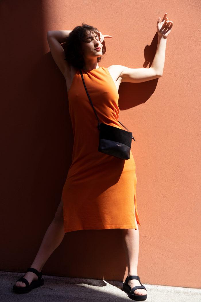 Model präsentiert schwarze Handtasche aus Leder von frisch Beutel