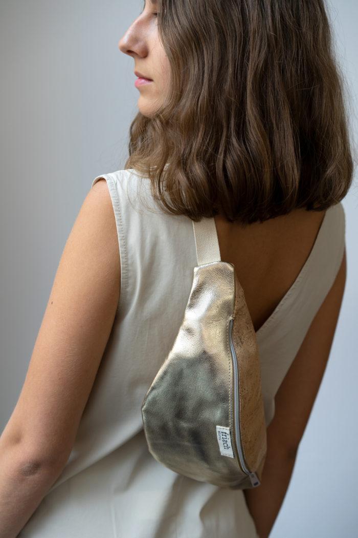 Model zeigt frisch Bauchtasche aus Kork und goldenem Leder