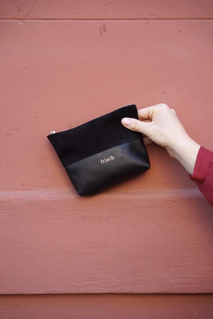 Hand zeigt kleines frisch Beutel Etui aus schwarzem Leder mit Kupfer vor roter Wand