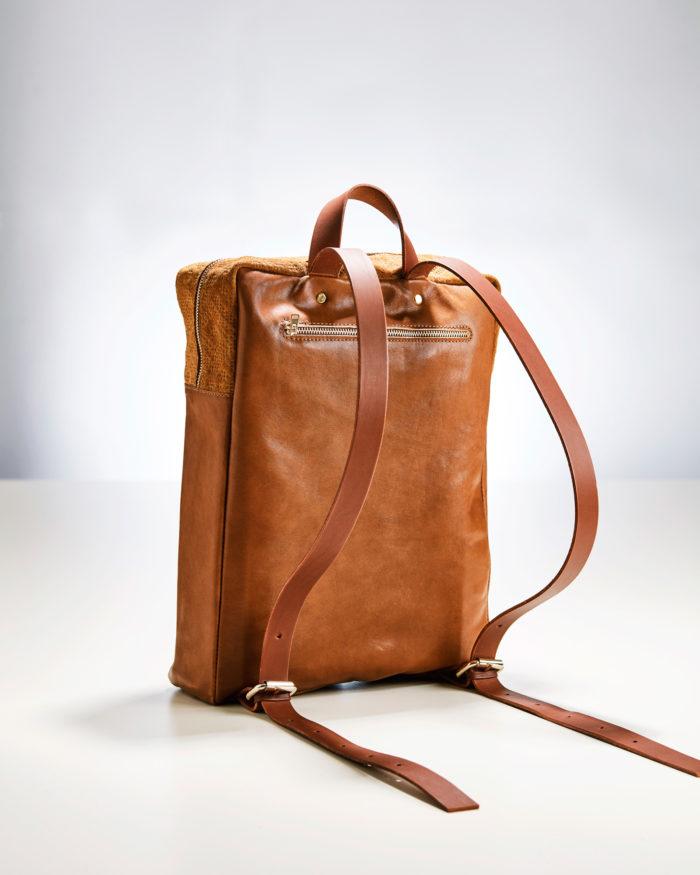 Rückseite einer braunen Lederrucksacks mit Reißverschlussfach