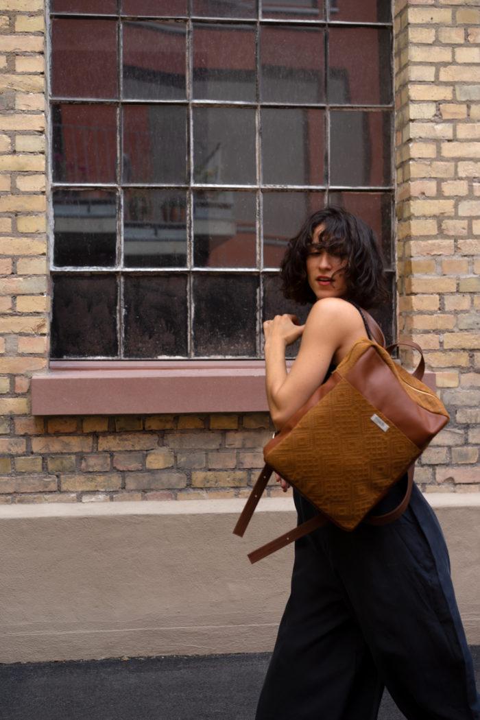 Tanzendes Model trägt braunen Boho Rucksack aus Leder