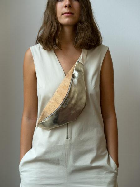 Model trägt Bauchtasche aus Kork und Gold schräg über Brust
