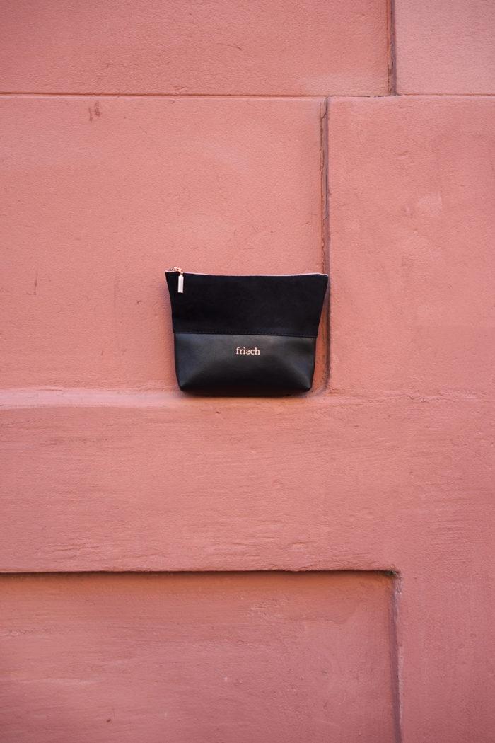 Kleiner frisch Beutel aus schwarzem Veloursleder und Glattleder mit Kupfer Reißverschluss präsentiert vor roter Wand