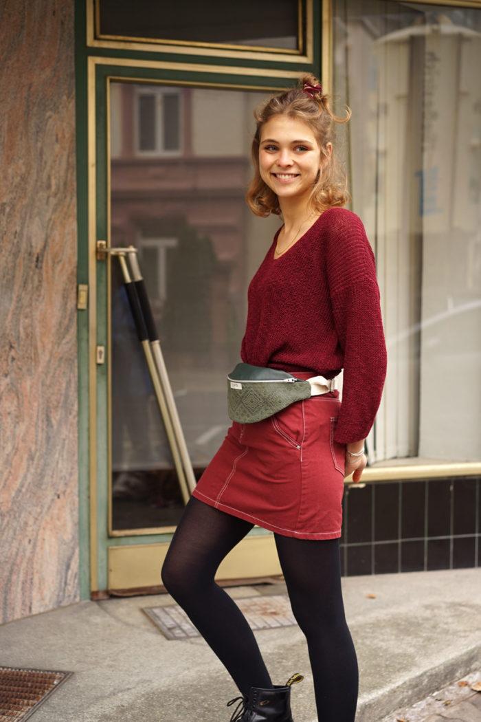 Model trägt rotes Outfit und grüne Bauchtasche mit Muster