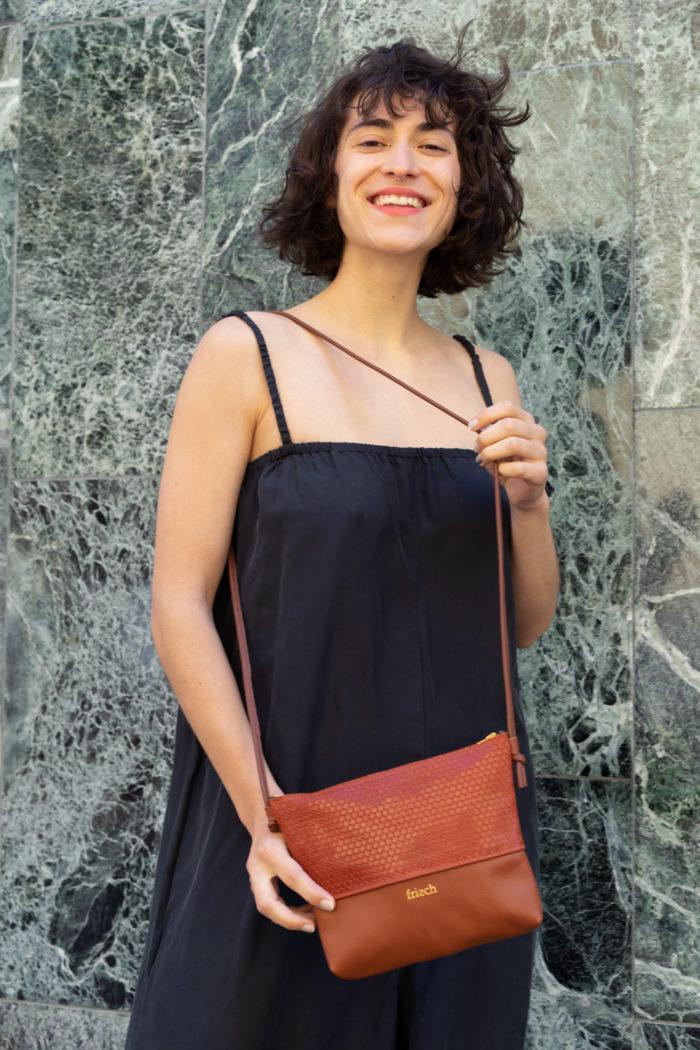 Handtasche aus rostrotem Leder zum Umhängen von Model getragen