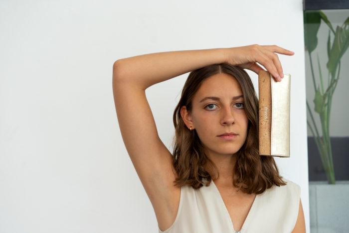 Model präsentiert Geldbeutel aus Kork und Gold von frisch Beutel