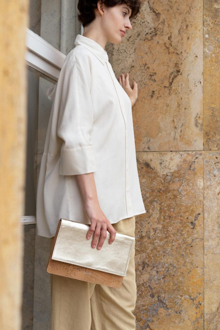 frisch Beutel Clutch aus Kork und goldenem Leder getragen von Model mit weißer Bluse