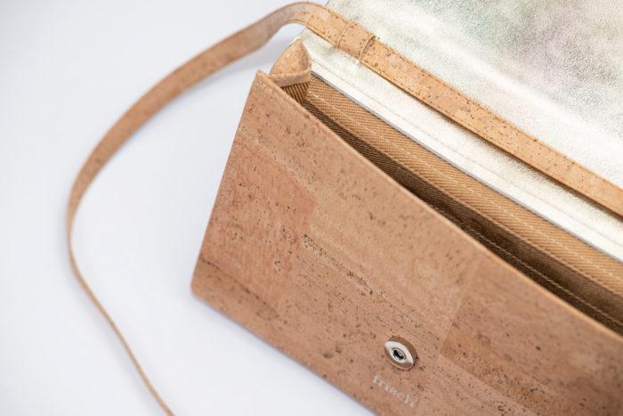 Detail einer Handtasche aus Kork und goldenem Leder mit silbernem Knopf