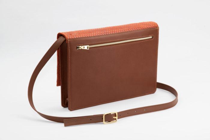 Rückseite einer braunen Handtasche mit goldenem Reißverschluss und verstellbarem Träger