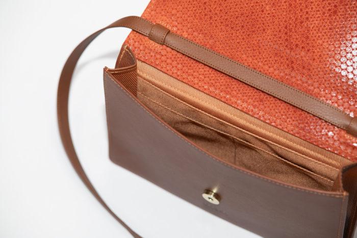 Innenfutter einer braunen Handtasche mit roter Klappe und braunem Lederträger