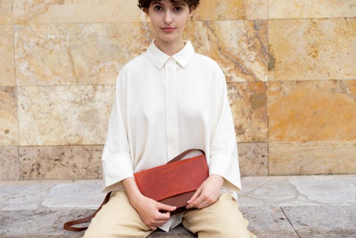 Model hält frisch Tasche für Damen aus rostrotem und braunem Leder