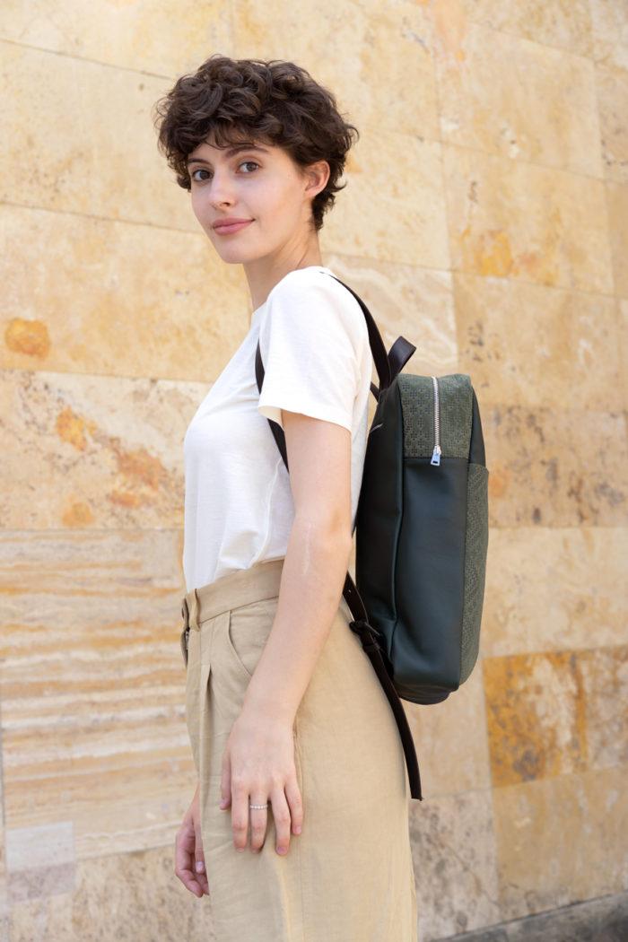 Model trägt frisch Beutel Rucksack Botanik in dunkelgrün mit Prägung