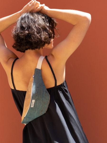 Vegane Korktasche crossover getragen von Model vor roter Wand
