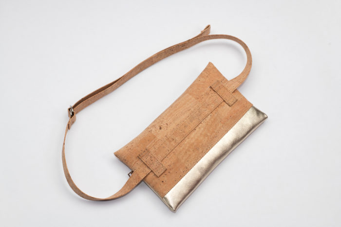 Rückseite einer eckigen Tasche aus Kork und goldenem Leder mit verstellbarem Träger auf weißem Hintergrund
