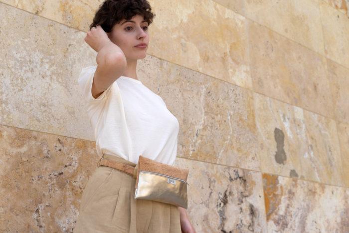 Model vor beigefarbener Steinwand mit frisch Beutel Gürteltasche aus Kork und goldenem Leder