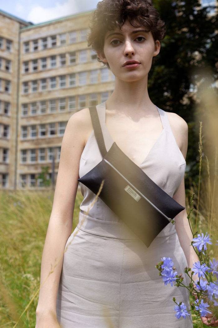 Vegane Gürteltasche aus Kork in schwarz von frisch Beutel getragen von Model auf Blumenwiese
