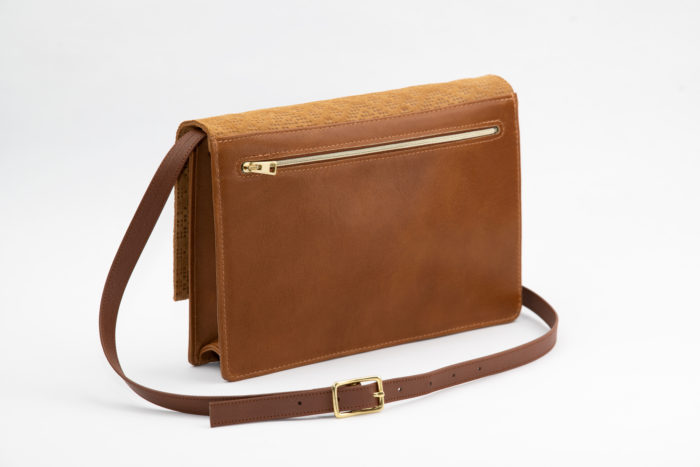 Rückseite einer Handtasche aus braunem Leder mit goldener Schnalle und Reißverschluss