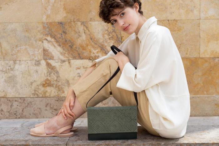 Model zeigt frisch Handtasche in dunkelgrünem Leder mit Klappe