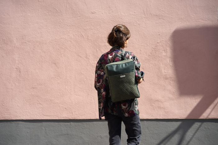 Dunkelgrüner Rucksack aus Leder mit Muster vor rosa Wand