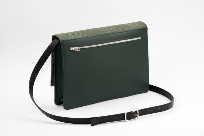 Rückseite einer grünen Handtasche mit Reißverschlussfach und schwarzem Träger