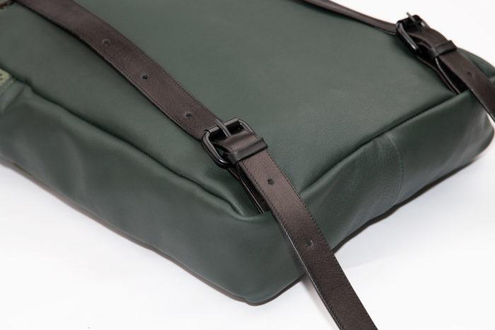 Detail eines grünen Rucksacks aus Leder mit schwarzen Schnallen und Trägern