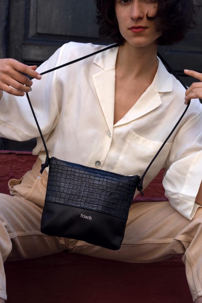 Model mit weißer Bluse und geprägter Handtasche von frisch Beutel in Kroko Optik