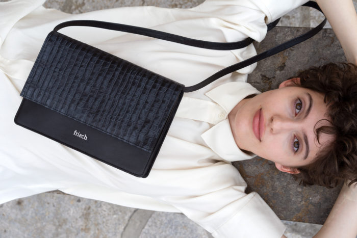 Model trägt im Liegen frisch Handtasche mit Kroko Prägung aus Leder mit Klappe
