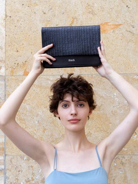 Model hält Handtasche mit Klappe von frisch Beutel über Kopf