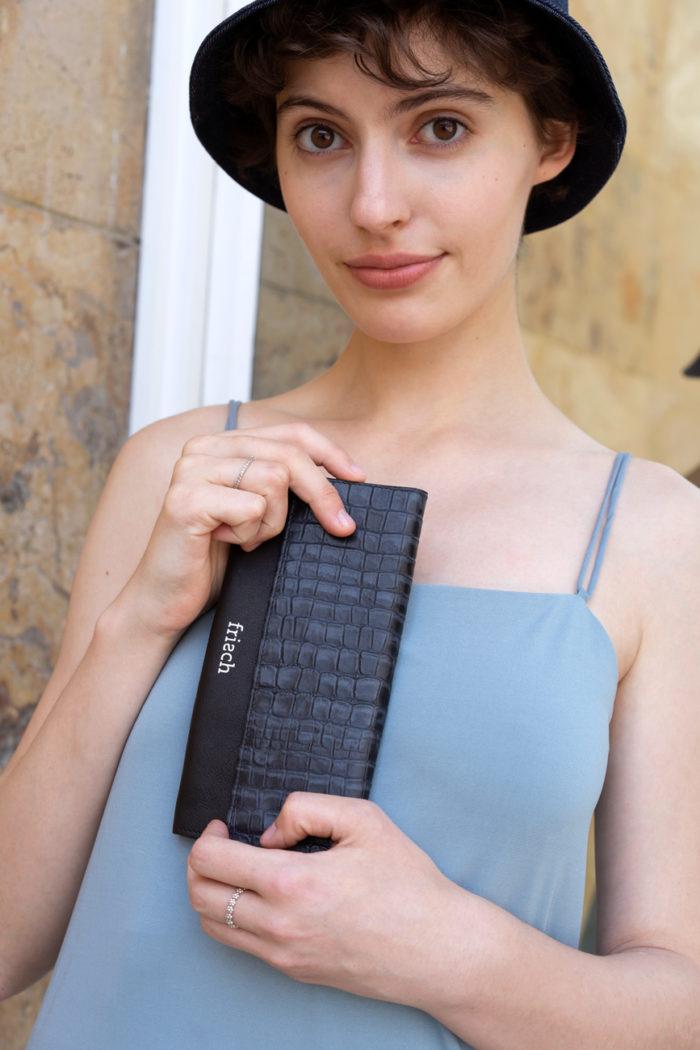 Model zeigt Geldbeutel in graublau mit Kroko Muster und frisch Logo Prägung