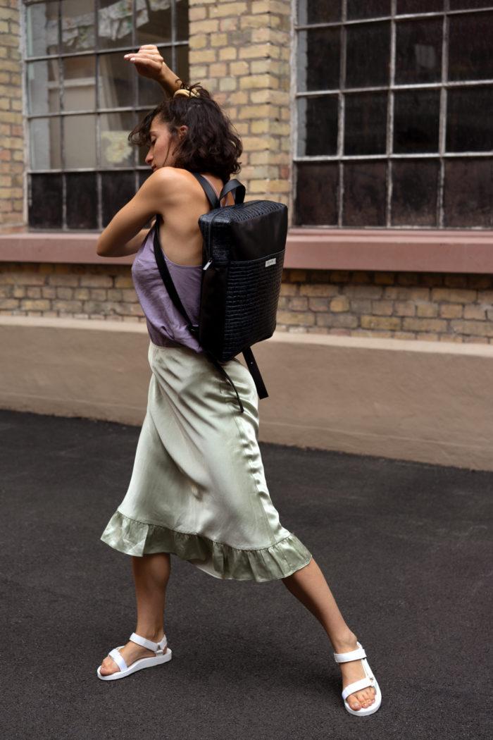 Tanzendes Model mit schickem Rucksack in schwarz
