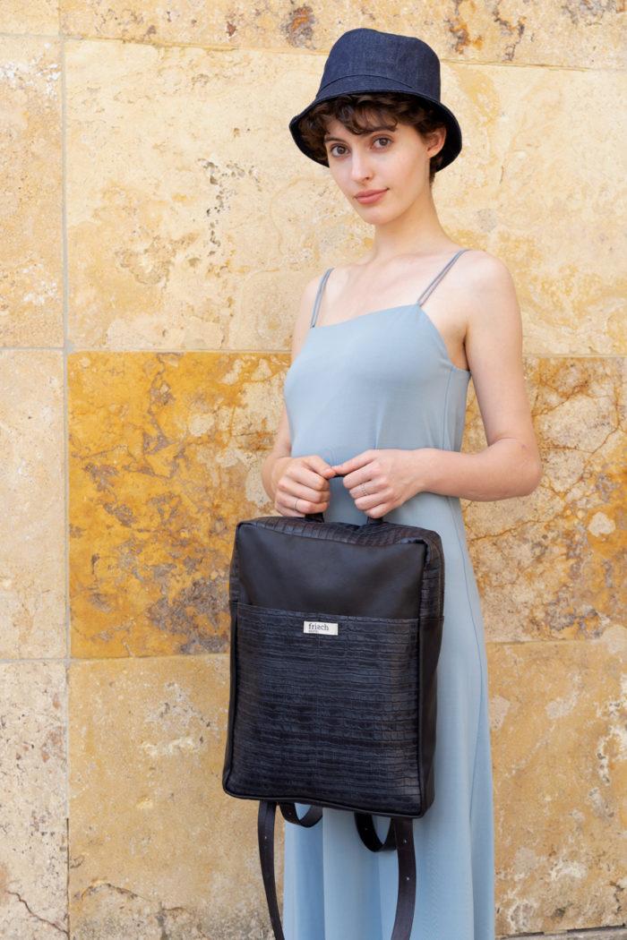 Model trägt graublauen frisch Rucksack Granit mit Kroko Muster