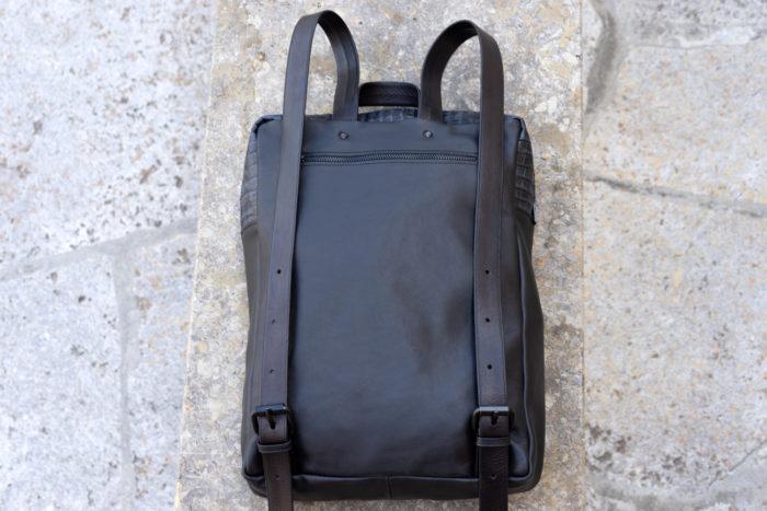 Rückseite eines schwarzen Rucksacks mit Lederriemen und Reißverschlussfach