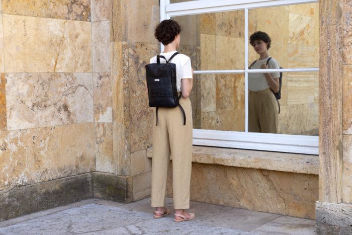 Model mit schickem Rucksack von frisch Beutel in schwarz und sandfarbener Hose