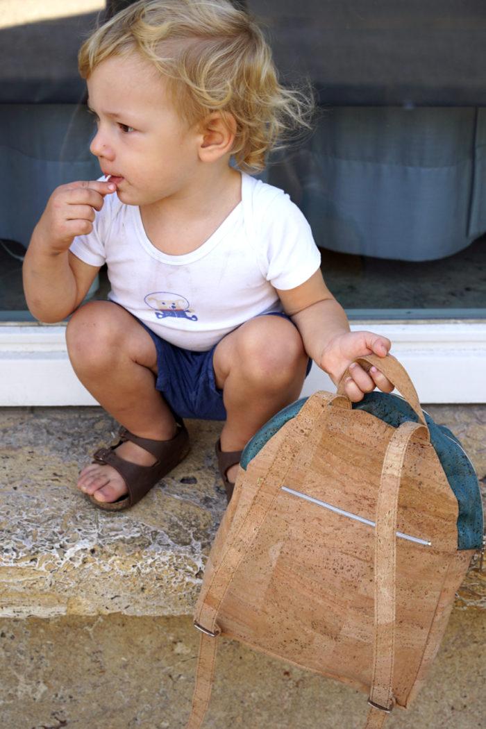 Junge mit Lutscher hält Rucksack für Kita aus Kork