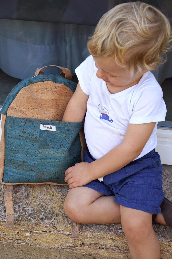 Junge greift in Außenfach von Rucksack für Kinder aus Kork