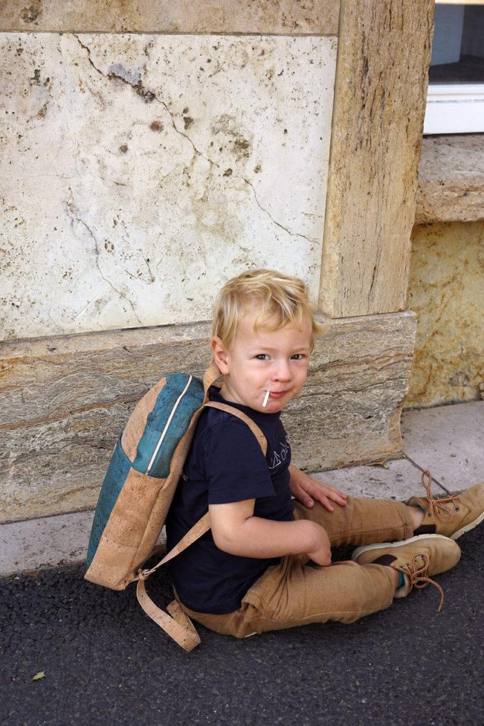 Kleiner Junge mit Rucksack aus Kork für Kinder sitzt auf dem Boden