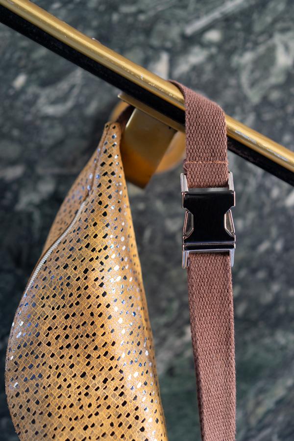 Detail einer Bauchtasche mit silber Schnalle und Baumwollband in senfgelb und braun