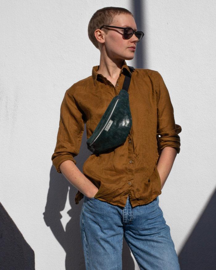 Dunkelgrüne Bauchtasche für Damen getragen von kurzhaarigem Model