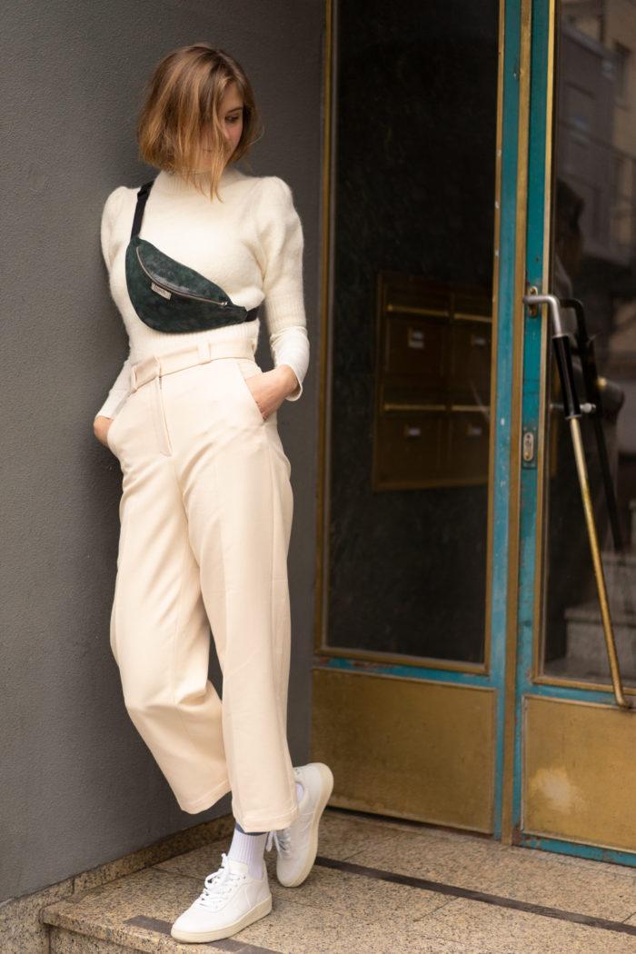 Model trägt frisch Beutel Hipbag Wood in dunkelgrün in Hauseingang